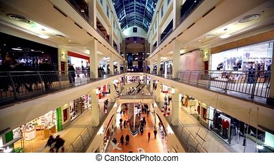 People walk along boutiques on multiple floors trade center