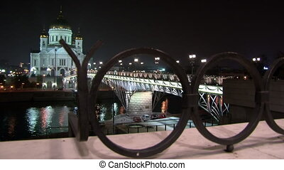 People walk along Patriarchal bridge to Cathedral of Christ Savior in Moscow.