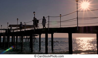 People walk along the pier, bridge. Sunset at the sea.