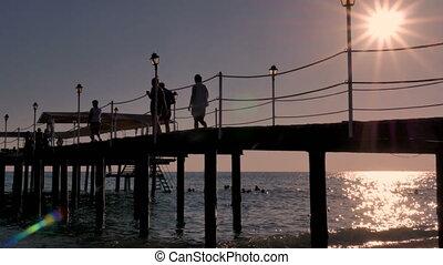 People walk along the pier, bridge. Sunset at the sea.
