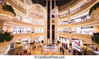 People walk and are engaged in purchases in shopping centre AfiMall City
