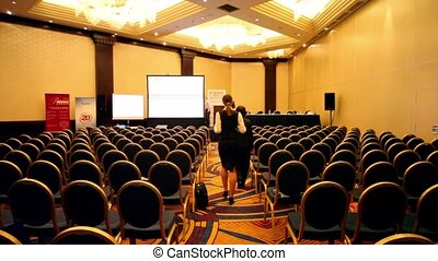 People walk in empty conference hall during the break
