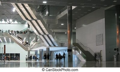People walk in enormous silver hall with big stairs, time...