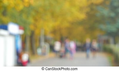 People walk in the autumn park. The crowd of unknown people blurred out of focus for background.