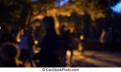 People walk in the evening in the Park on the waterfront. Bright lights, blur
