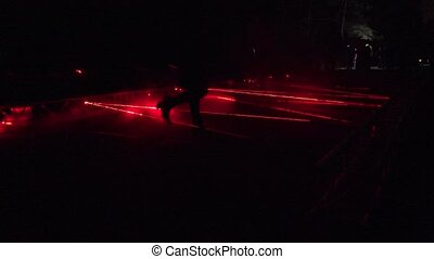 People walk laser formed red lines in park night light show....