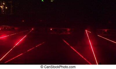 People walk laser formed red lines night light show. 4K -...