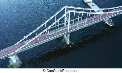 People walk on a footbridge over a river with a cargo barge filled with sand - Walk along the city pedestrian bridge. Drone tilt Down shot.