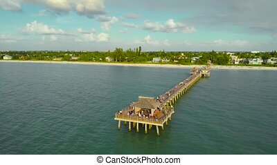 People walk on a pier in Naples, Florida to watch the sunset. Sunset over the Gulf of Mexico, Drone flying above pier. Camera flies over the pier running into the ocean.