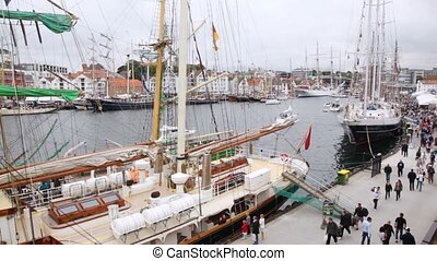 People walk on pier near sailing ships which profits on...