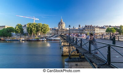People walk on the Bridge of Arts over the River Seine between the Institute of France and the Louvre timelapse hyperlapse - Paris, France