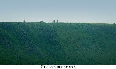 People Walking Along Hilltop