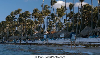 People walking along the beach on tropical resort