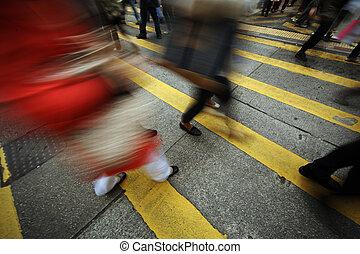 People walking over yellow zebra crosswalk. Long exposure, blurred motion.