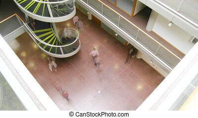 People walking in a business building quickly