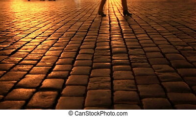 People walking in a cobblestone street at night
