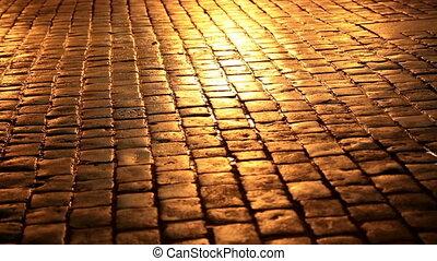 People walking in a cobblestone street at night - People...