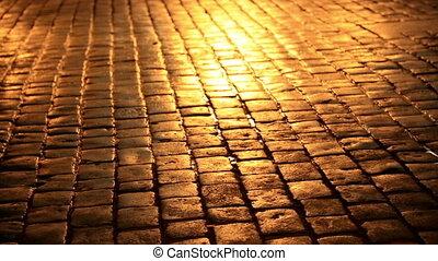People walking in a cobblestone street at night