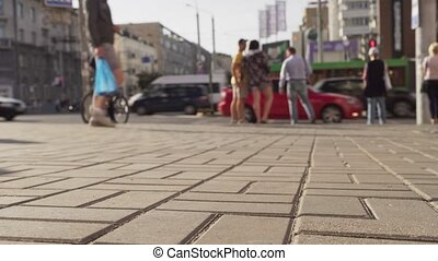 People walking in city in front of road with lively car traffic on summer day