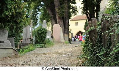 People Walking in Old Cemetery - People walking on...