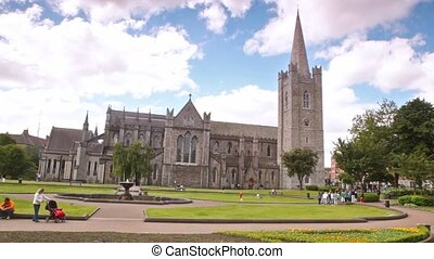 people walking in park near magnificent Saint Patrick's Cathedral in Dublin