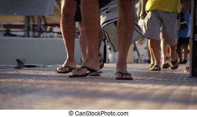 People walking in pier - A worm's eye view of people's feet...