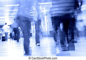 people walking in subway - motion blurred of people walking...