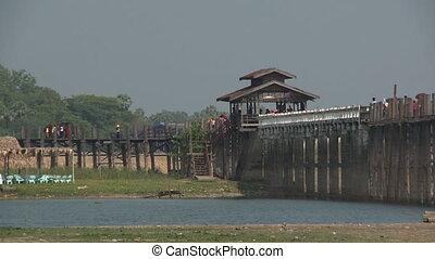 People walking on a bridge across a lake