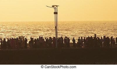 People walking on a seawall