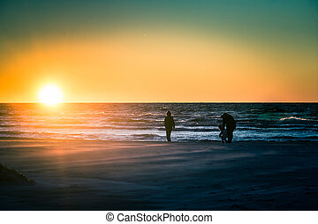 People walking on a sunset beach, picking ambers. Nice evening walk with family. Winter sunset at the Baltic sea.