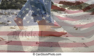 Animation of U.S. flag waving with U.S. Constitution text rolling over Caucasian couple walking barefoot on a beach. United States of America flag and holiday concept digital composition