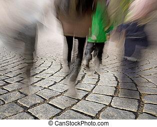 People walking on cobble stones - Legs of people in blurred ...