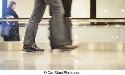 People walking on moving staircase with luggage in the international airport, close up shot of legs and shoes