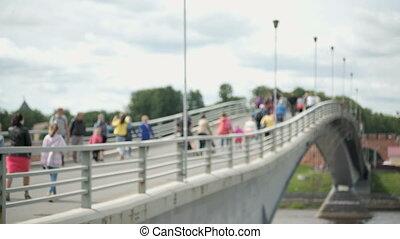 People walking on pedestrian bridge over river
