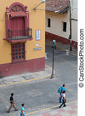 People Walking on the street next to a red yellow colonial house and corner in Leon