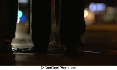 People walking over steaming manhole at night