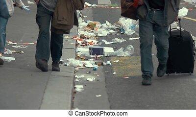 People walking past garbage. Trash on city road. Danger...