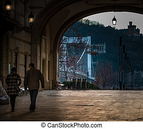 People walking through arch in Budapest.