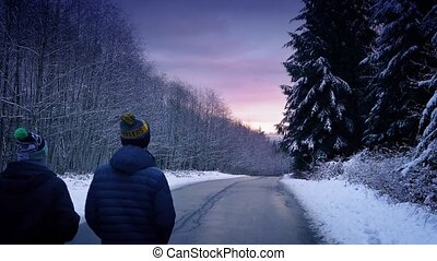 People Walking Through Snowy Woods At Sunset