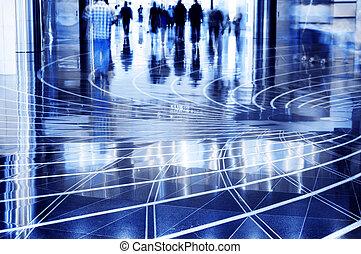 People walking thru the mall. - A shopping mall. Long...