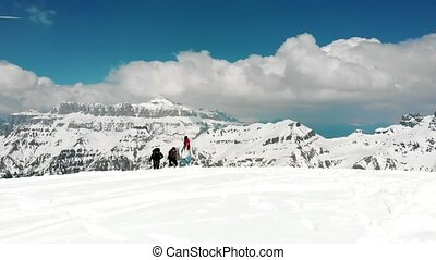 People walking upwards on the snow in Dolomites with big...