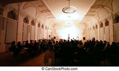 People watch arabian dancer performance in concert hall