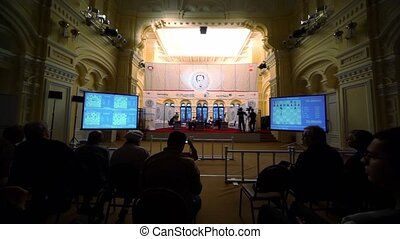 People watch chess tournament, current positions at chessboards are shown on screens