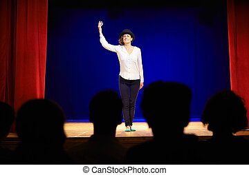 People watching actress on theater stage during play - Arts...