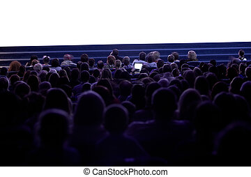 Wide shot of sihouettes of people from back watching cinema. Somebody filming the movie using tablet. Empty cinema screen
