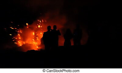People Watching Lava - Silhouettes of sightseers in front of...