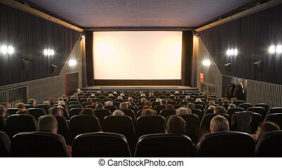 Cinema auditorium with people sitting in chairs and watching screen. Ready for adding your own picture.