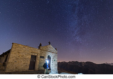 The Milky Way and the starry sky from high up on the Alps with scenic mountain landscape. People standing aside a little chapel with lightning gear on.