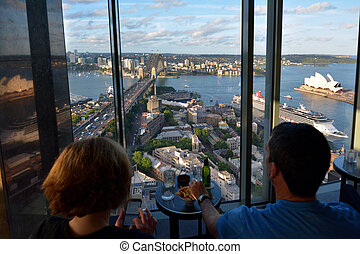 People watching the landscape view of Sydney Harbour at sunset
