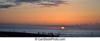 People watching the sunset on Atlantic Ocean shore
